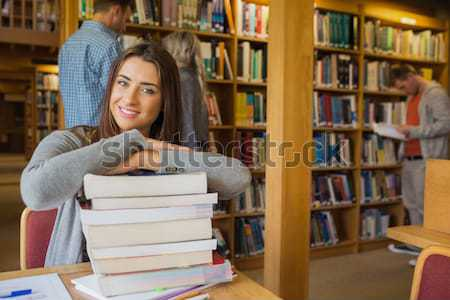Portrait of college student sitting with stack of books in libra Stock photo © wavebreak_media