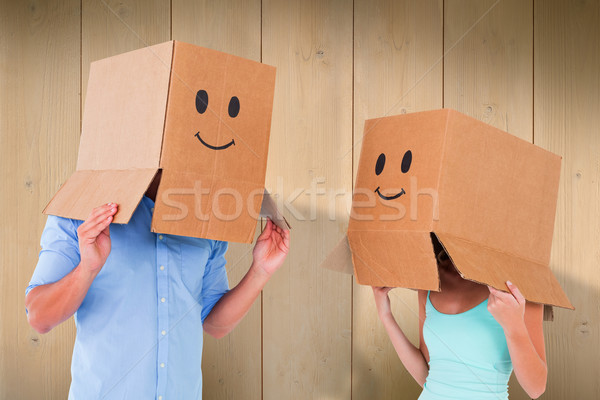 Composite image of couple wearing emoticon face boxes on their h Stock photo © wavebreak_media