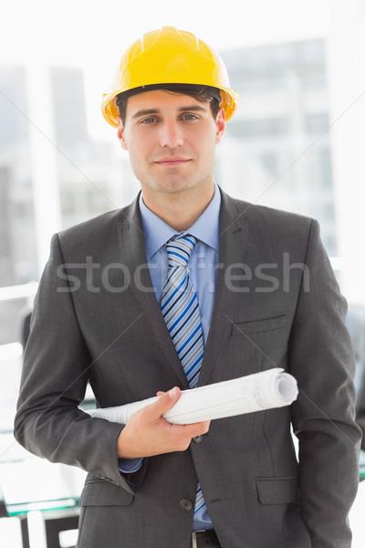 Happy architect holding blueprints looking at camera Stock photo © wavebreak_media