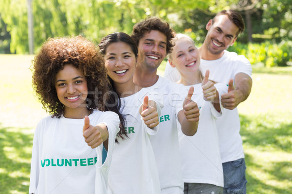 Confident volunteers gesturing thumbs up  Stock photo © wavebreak_media