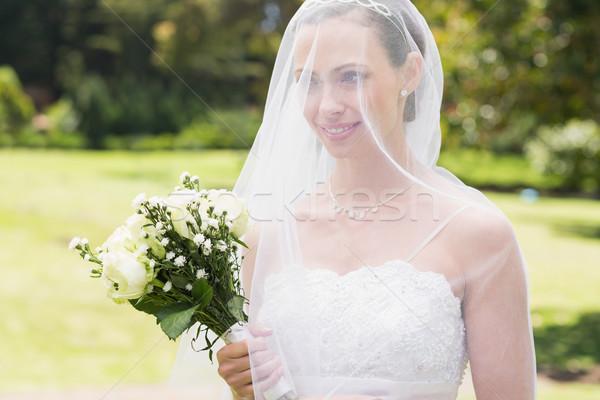 Bride looking away through veil in garden Stock photo © wavebreak_media