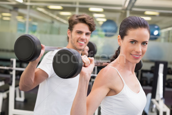 Fit couple lifting barbells together Stock photo © wavebreak_media