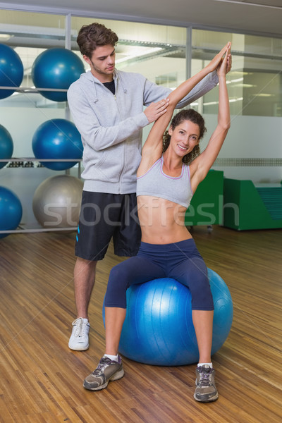 Trainer helping his client stretch on exercise ball Stock photo © wavebreak_media