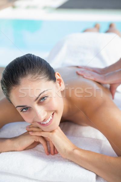 Happy brunette enjoying a massage poolside Stock photo © wavebreak_media
