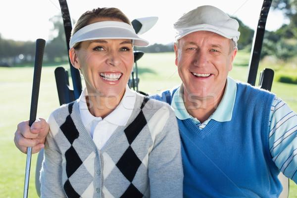 Happy golfing couple sitting in golf buggy smiling at camera Stock photo © wavebreak_media