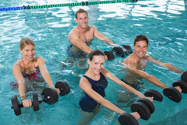 Stock photo: Happy fitness class doing aqua aerobics with foam dumbbells