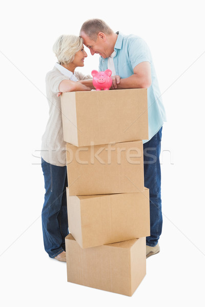 Older couple smiling at each other with moving boxes and piggy b Stock photo © wavebreak_media