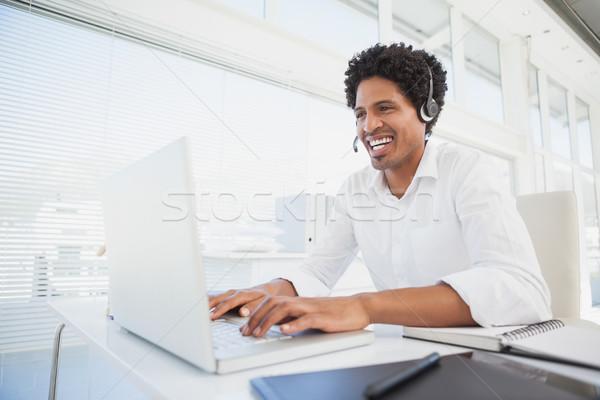Happy businessman working at his desk wearing headset Stock photo © wavebreak_media