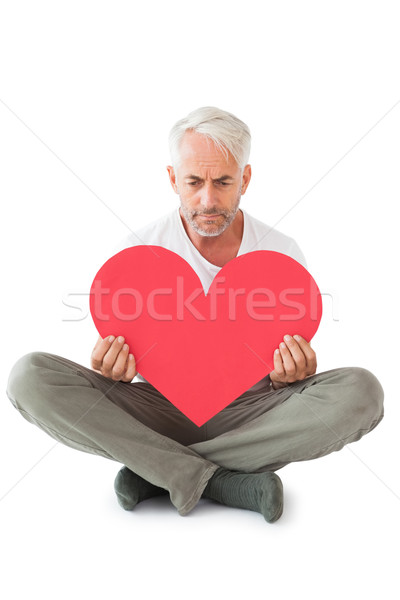 Chateado homem sessão forma de coração branco Foto stock © wavebreak_media