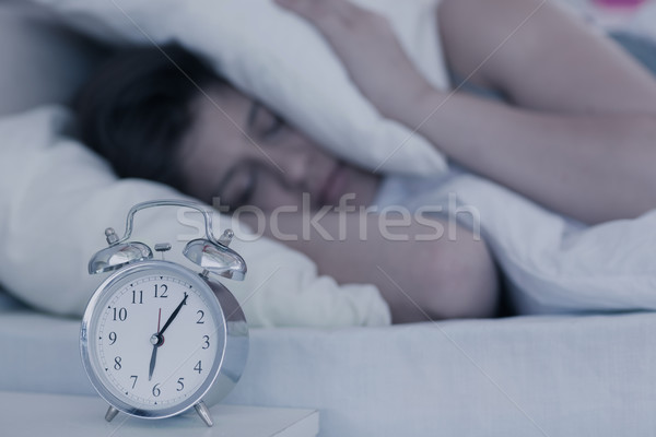 Beautiful brunette blocking the noise from alarm clock in her be Stock photo © wavebreak_media