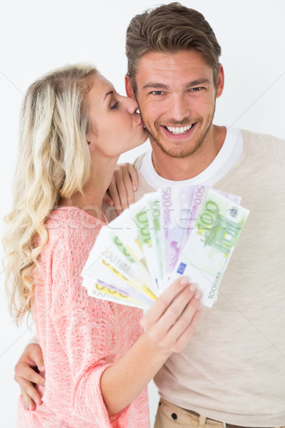 Woman kissing man as she holds banknotes Stock photo © wavebreak_media