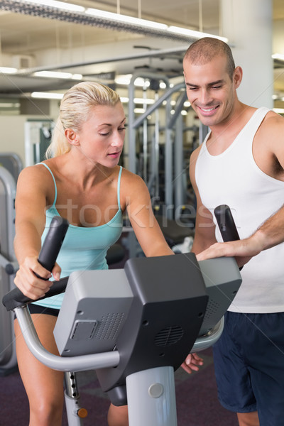 Trainer assisting woman with exercise bike at gym Stock photo © wavebreak_media