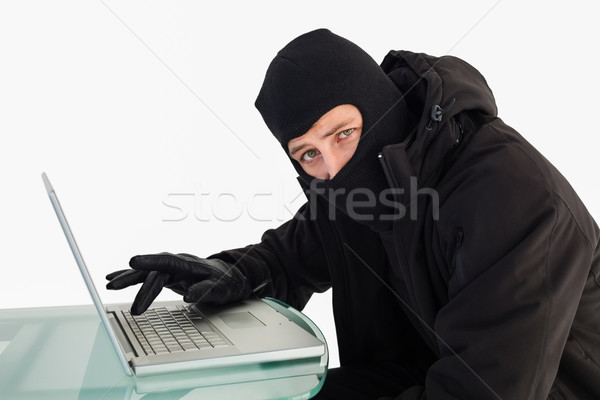 Hırsız dizüstü bilgisayar kullanıyorsanız bakıyor kamera beyaz bilgisayar Stok fotoğraf © wavebreak_media