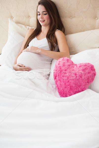 Zwangere brunette vergadering bed home slaapkamer Stockfoto © wavebreak_media