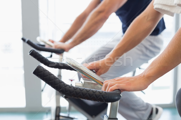 Mid section of couple working on exercise bikes at gym Stock photo © wavebreak_media