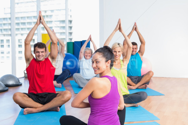 Instructor with class practicing yoga in fitness studio Stock photo © wavebreak_media