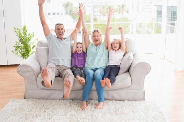 Család négy karok a magasban ül kanapé boldog család Stock fotó © wavebreak_media