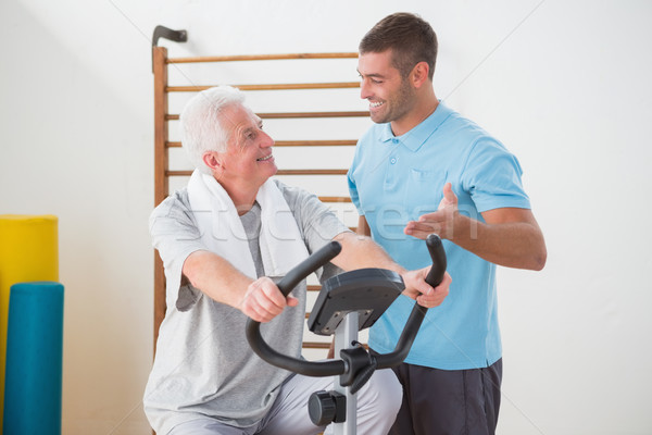 Senior man doing exercise bike with his trainer  Stock photo © wavebreak_media