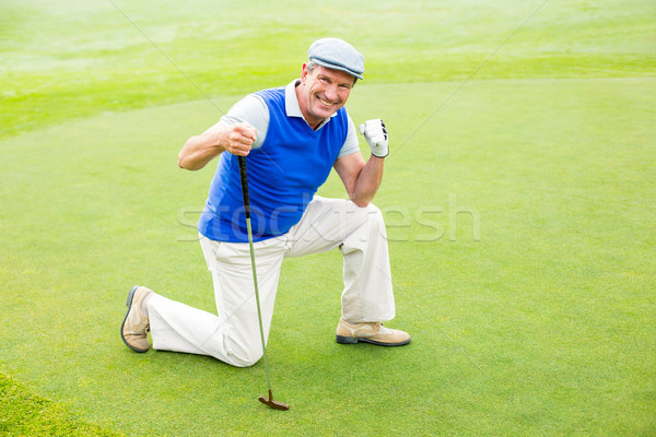 Smiling golfer kneeling on the putting green  Stock photo © wavebreak_media