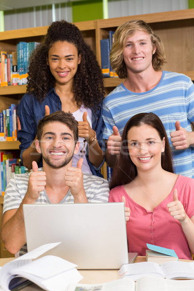 College students gesturing thumbs up in library Stock photo © wavebreak_media