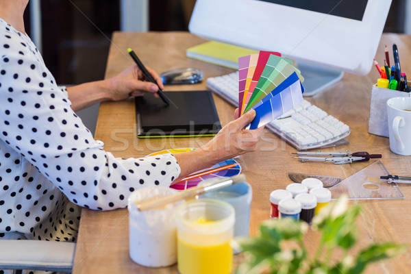 Casual businesswoman looking at colour swatch and drawing with d Stock photo © wavebreak_media