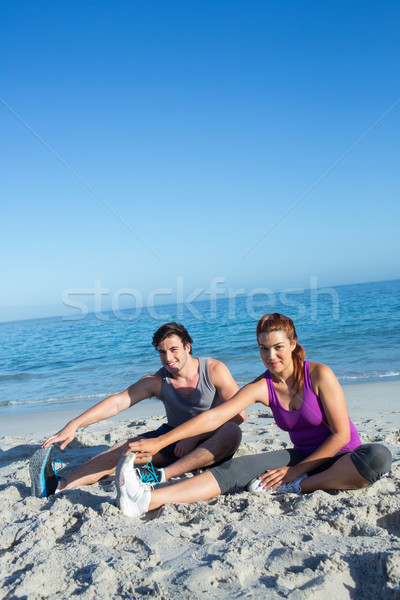 Happy couple stretching together beside the water Stock photo © wavebreak_media