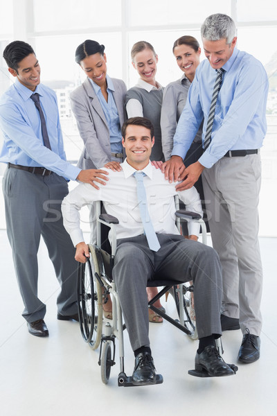 Business people supporting their colleague in wheelchair  Stock photo © wavebreak_media