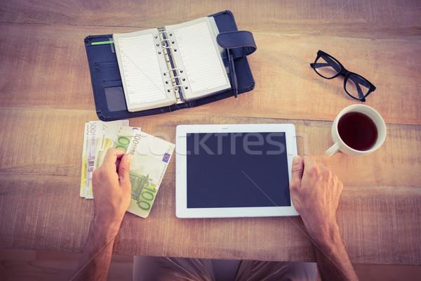 Money bundle and digital tablet on the table Stock photo © wavebreak_media