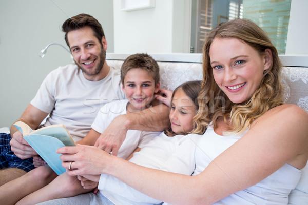 счастливая семья кровать чтение книга домой спальня Сток-фото © wavebreak_media