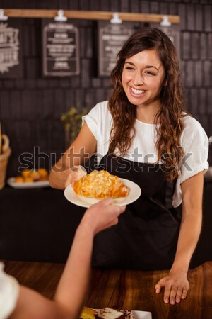 Pretty waitress smelling a plate of cake Stock photo © wavebreak_media