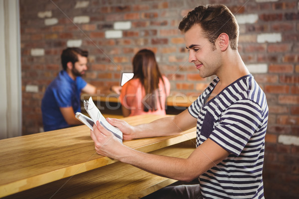 Stock photo:  Young man reading a newspaper