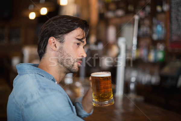 Man looking away while drink beer at pub Stock photo © wavebreak_media