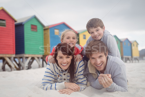 Portrait of happy parents with children lying on sand Stock photo © wavebreak_media