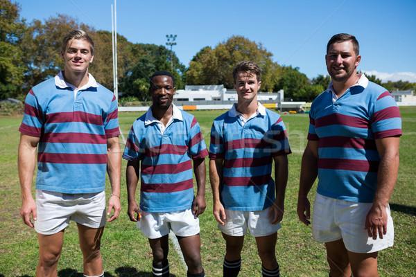 Portrait of smiling rugby team standing on grassy field Stock photo © wavebreak_media