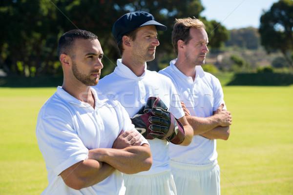 Confident cricket players standing at grassy field Stock photo © wavebreak_media