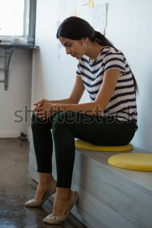 Thoughtful rugby player with ball sitting in locker room Stock photo © wavebreak_media