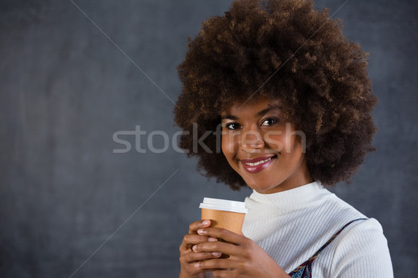 Smiling woman holding disposable coffee cup against wall Stock photo © wavebreak_media