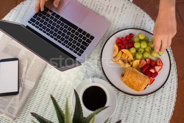 Stock photo: Cropped hands having fruit while using laptop