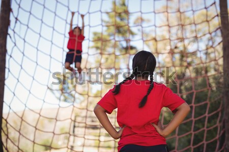 Trainer instructing kids in net climbing during obstacle course training Stock photo © wavebreak_media