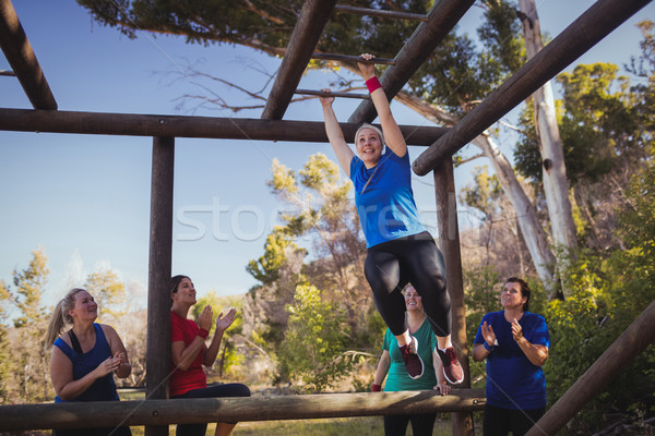 Woman being cheered bye her teammates to climb monkey bars during obstacle course training Stock photo © wavebreak_media