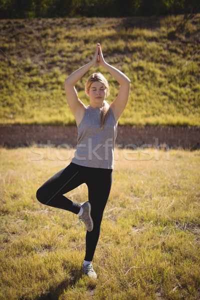 Beautiful woman praising yoga during obstacle course Stock photo © wavebreak_media