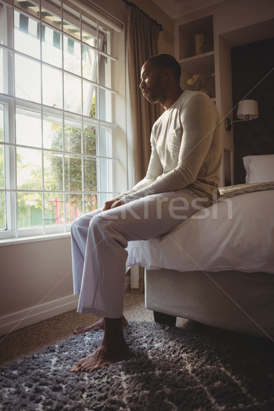 Full length of thoughtful man sitting on bed by window Stock photo © wavebreak_media