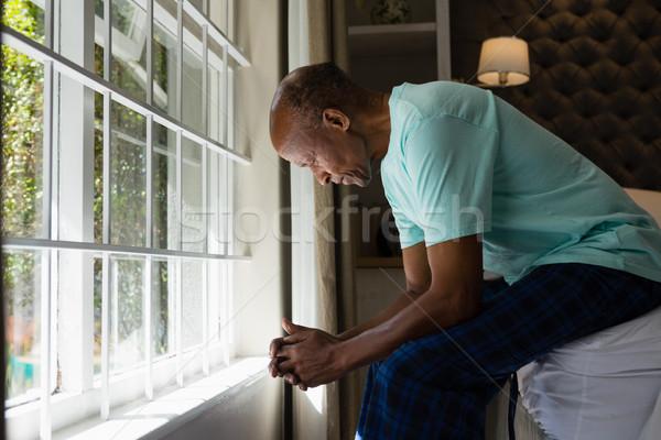 Senior man sitting by window in bedroom at home Stock photo © wavebreak_media