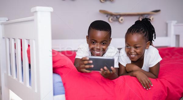 Testvérek mobiltelefon ágy otthon boldog piros Stock fotó © wavebreak_media