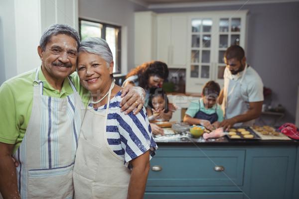 Senior couple smiling at camera while family members preparing dessert in background Stock photo © wavebreak_media