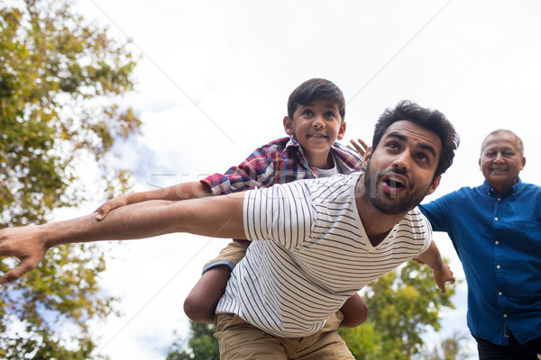 Smiling grandfather looking at man giving piggy backing to son Stock photo © wavebreak_media
