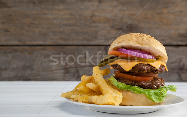 Hamburger and french fries in plate on wooden table Stock photo © wavebreak_media