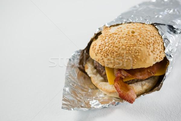 Közelkép hamburger papír asztal fehér mosolyog Stock fotó © wavebreak_media