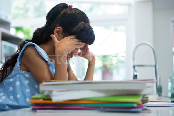 Side view of exhausted girl sitting by books in kitchen Stock photo © wavebreak_media