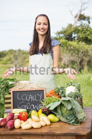 Stock photo: Portrait of happy woman holding fresh carrots at vegetable stall